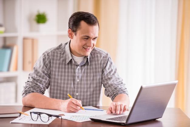Dobry mężczyzna siedzi przy stole w domu i korzysta z laptopa. Premium Zdjęcia