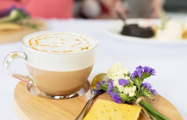 Dobrze Udekorowany Kubek Gorącej Kawy Podawany Na Danie Drewniane I Mały Fioletowy Kwiat I Herbatniki Darmowe Zdjęcia