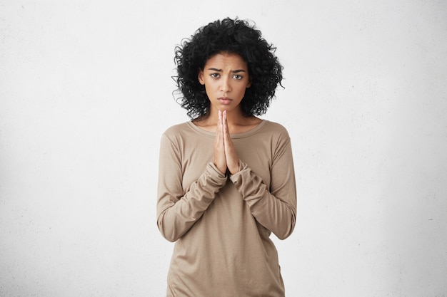 Dobrze Wyglądająca Kobieta Ubrana Niedbale, Trzymając Dłonie Złączone Przed Sobą, Z żałosnym I żałosnym Spojrzeniem, Błagająca O Wybaczenie. Wyraz Twarzy, Emocje I Język Ciała Człowieka Darmowe Zdjęcia