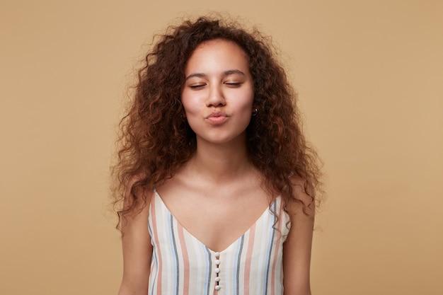 Dobrze Wyglądająca Młoda, Pozytywna, Kręcona Brunetka Dama Z Zamkniętymi Oczami, Zaciskając Usta W Pocałunku W Powietrzu, Ubrana W Swobodną Bluzkę, Stojąc Na Beżu Darmowe Zdjęcia