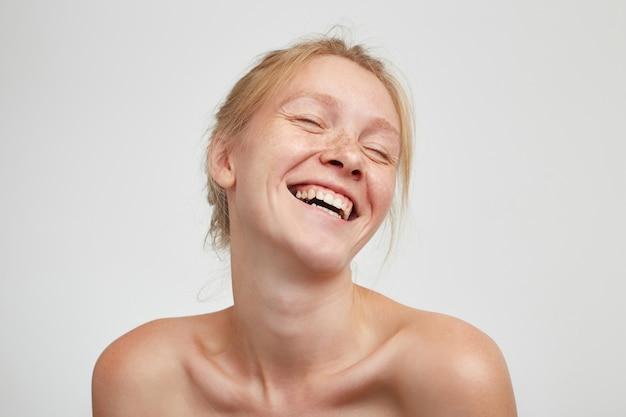 Dobrze Wyglądająca Młoda Urocza Wesoła Ruda Dama Z Naturalnym Makijażem, Pokazująca Swoje Białe Idealne Zęby, Uśmiechając Się Szeroko, Pozując Na Białym Tle Darmowe Zdjęcia