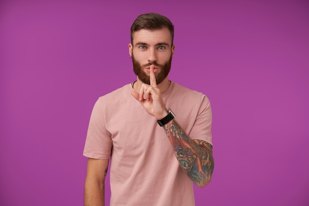 Dobrze Wyglądający Młody Brodaty Brunet Z Tatuażami Trzymający Palec Wskazujący Na Ustach W Znaku Ciszy, Proszący O Zachowanie Tajemnicy, Ubrany W Beżową Koszulkę I Modne Akcesoria Podczas Pozowania Na Fioletowo Darmowe Zdjęcia