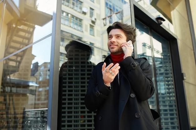 Dobrze Wyglądający Młody Przystojny Brodaty Brunetka Mężczyzna W Eleganckich Ubraniach Trzymając Telefon Komórkowy W Uniesionej Ręce, Mając Przyjemną Rozmowę, Odizolowane Na Tle Miasta Darmowe Zdjęcia