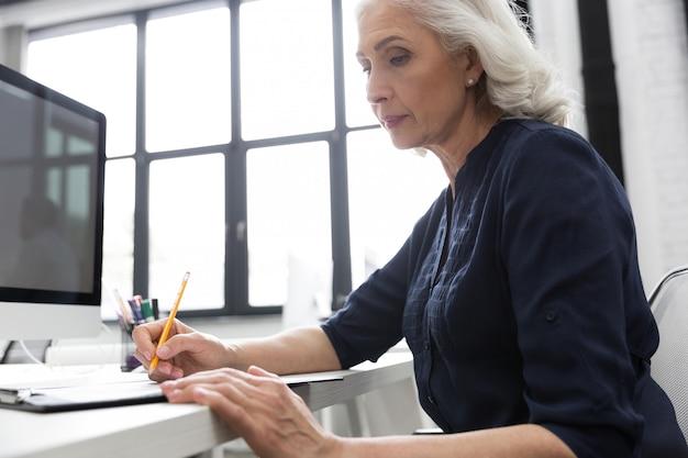 Dojrzała Biznesowa Kobieta Robi Notatkom Na Kawałku Papieru Darmowe Zdjęcia