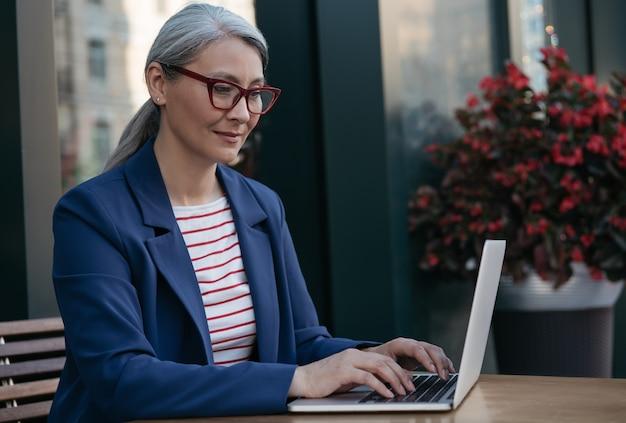 Dojrzała Bizneswoman Przy Użyciu Komputera Przenośnego, Pracując W Trybie Online Premium Zdjęcia