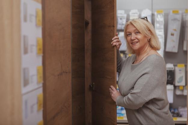 Dojrzała kobieta robi zakupy przy meblarskim sklepem Premium Zdjęcia