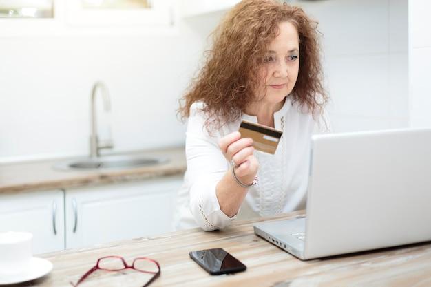Dojrzała Kobieta Trzyma Kartę Kredytową I Używa Laptopa W Domu. Zakupy Online, Handel Elektroniczny I Bankowość Internetowa Z Koncepcji Domu. Premium Zdjęcia
