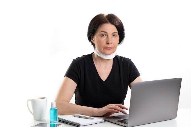 Dojrzała Kobieta W Medycznej Masce Pracuje Przy Laptopem. Obok Kubka Z Kawą Lub Herbatą Odkażacz Do Rąk. Premium Zdjęcia