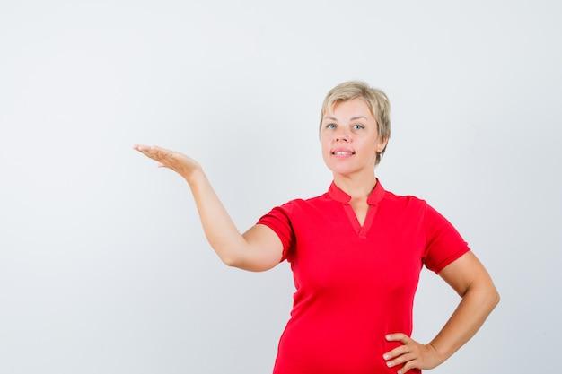 Dojrzała Kobieta Witająca Lub Pokazująca Coś W Czerwonej Koszulce I Wyglądająca Na Pewną Siebie. Darmowe Zdjęcia