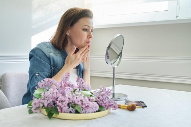 Dojrzała kobieta z makijażu lustrem masuje jej twarz i szyję Premium Zdjęcia