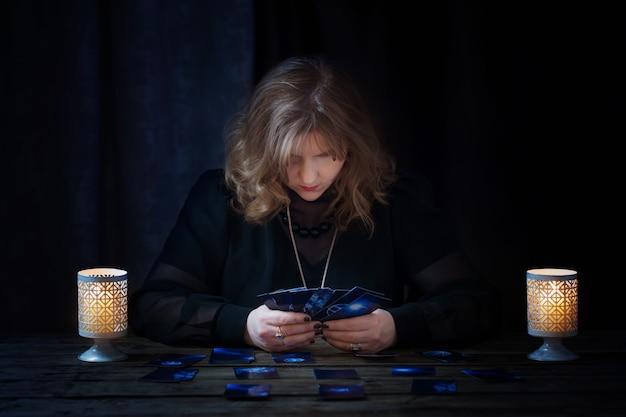 Dojrzała Kobieta Zgaduje Z Kartami Na Zmroku Premium Zdjęcia
