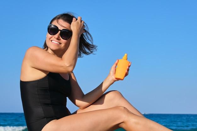 Dojrzała Piękna Kobieta Siedzi Na Plaży Za Pomocą Kremu Przeciwsłonecznego Premium Zdjęcia
