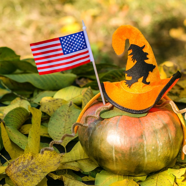 Dojrzała Pomarańczowa Dynia Ozdobiona Kapeluszem Halloween, Leży Na żółtych Jesiennych Liściach. Premium Zdjęcia