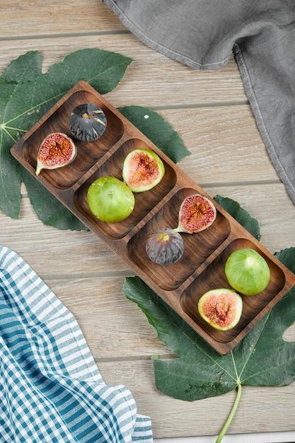 Dojrzałe Figi W Całości Oraz Plastry Zielono-czarne Figi Na Drewnianym Talerzu Z Listkiem I Obrusem. Darmowe Zdjęcia
