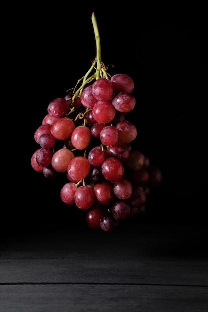 Dojrzałe Kiść Czerwonych Winogron Lewitujących Na Czarno Premium Zdjęcia