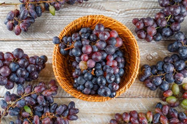 Dojrzałe Winogrona W Wiklinowym Koszu Na Drewnianym Tle. Leżał Płasko. Darmowe Zdjęcia
