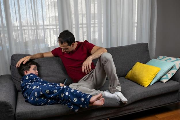 Dojrzały 44-letni Mężczyzna Siedzi Obok 7-letniego Syna I Głaszcze Się Po Głowie. Premium Zdjęcia