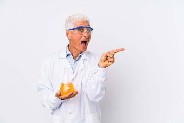 Dojrzały Chemik Na Białym Tle, Wskazując Na Bok Premium Zdjęcia