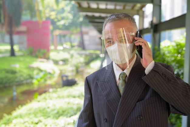 Dojrzały Japoński Biznesmen Opowiada Na Telefonie Przy Parkiem Z Maską I Twarzy Osłoną Premium Zdjęcia