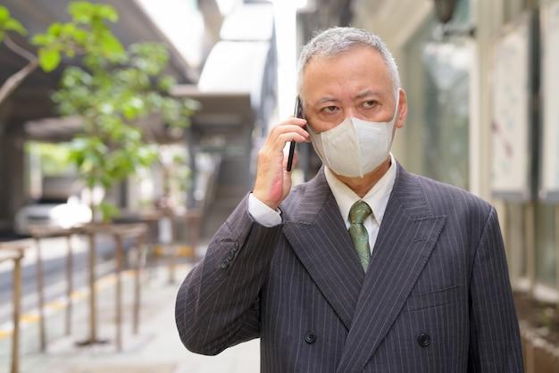 Dojrzały Japoński Biznesmen Opowiada Na Telefonie W Mieście Z Maską Premium Zdjęcia