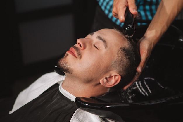 Dojrzały mężczyzna dostaje nową fryzurę w zakładzie fryzjerskim Premium Zdjęcia