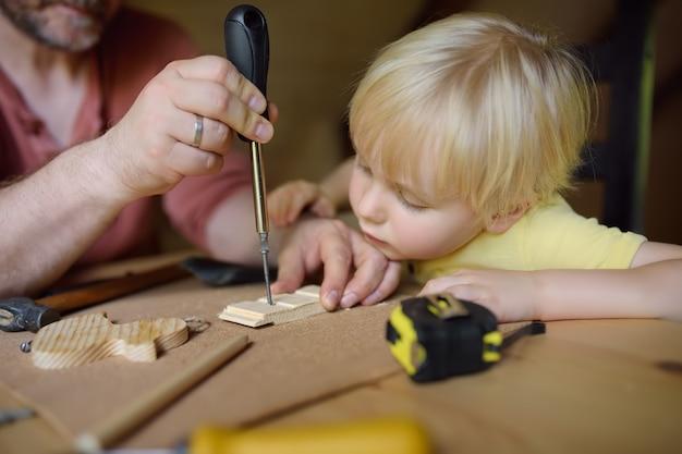 Dojrzały Mężczyzna I Mały Chłopiec Razem Tworzą Drewnianą Zabawkę. Premium Zdjęcia