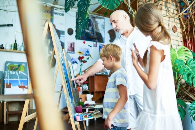 Dojrzały Nauczyciel Pomaga Dzieciom W Pracowni Artystycznej Premium Zdjęcia