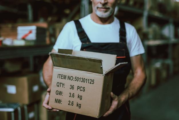 Dojrzały pracownik magazynu gospodarstwa pudełko z towarami Premium Zdjęcia