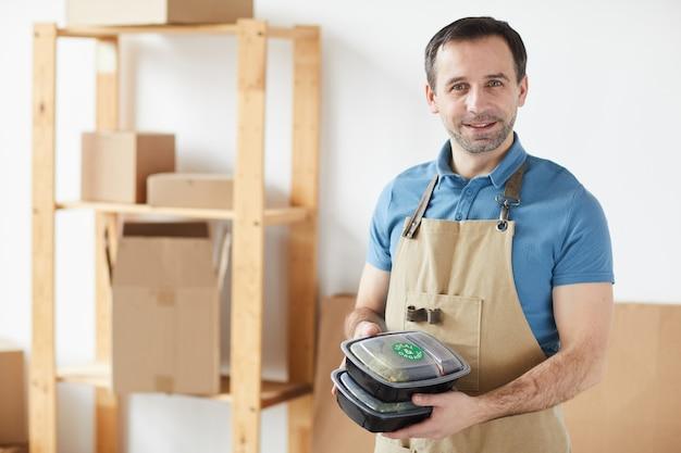 Dojrzały Pracownik Ubrany W Fartuch I Uśmiechnięty, Trzymając Zamówienia Na Dostawę żywności Premium Zdjęcia