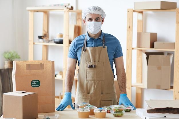 Dojrzały Pracownik Ubrany W Odzież Ochronną Podczas Bezpiecznego Pakowania Zamówień Przy Drewnianym Stole W Usłudze Dostawy żywności Premium Zdjęcia