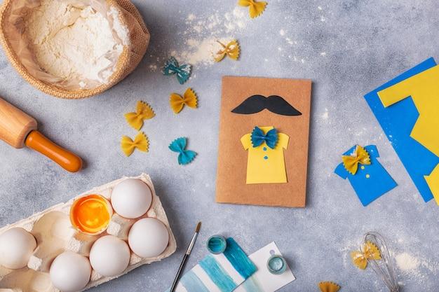 Dokonywanie kartkę z życzeniami na dzień ojca. koszula z motylkiem z makaronu. karta z papieru. wąsy. projekt artystyczny dla dzieci. Premium Zdjęcia