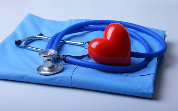 Doktor fartuch medyczny stetoskop i czerwone serce na biurku Premium Zdjęcia