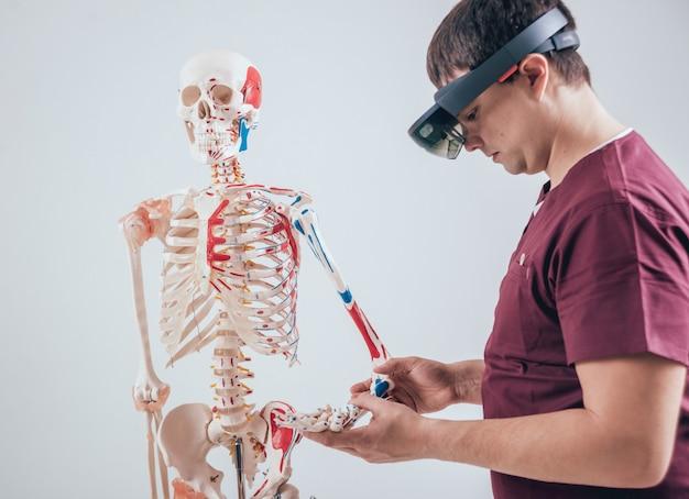 Doktor Używa Okularów Rzeczywistości Rozszerzonej Do Badania Ludzkiego Szkieletu Premium Zdjęcia
