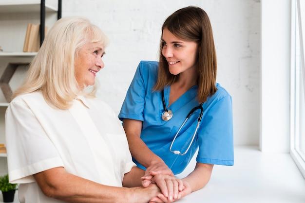 Doktorska i stara kobieta trzyma ręki Darmowe Zdjęcia