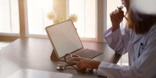 Doktorska Kobieta Pracuje Z Pastylką I Pisze Na Papierkowej Robocie W Biurowym Pokoju Premium Zdjęcia