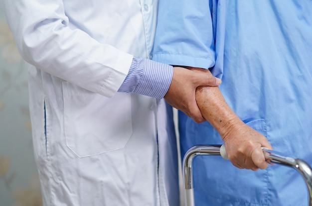Doktorska pomoc i opieka azjatycka starsza kobieta używa chodzika. Premium Zdjęcia