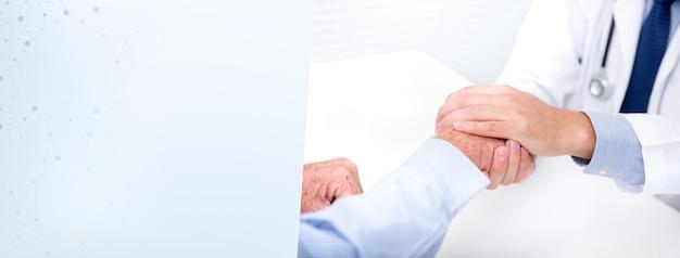 Doktorski pocieszający pacjenta trzymać jego rękę w szpitalu - sztandaru tło Premium Zdjęcia