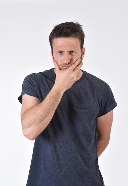 Dokuczający i zadumany mężczyzna na bielu Premium Zdjęcia