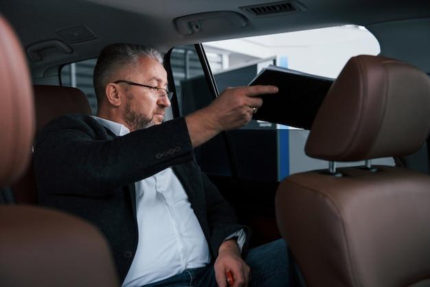 Dokumenty Przez Otwarte Okno. Dokumenty Na Tylnym Siedzeniu Samochodu. Starszy Biznesmen Z Dokumentami Darmowe Zdjęcia