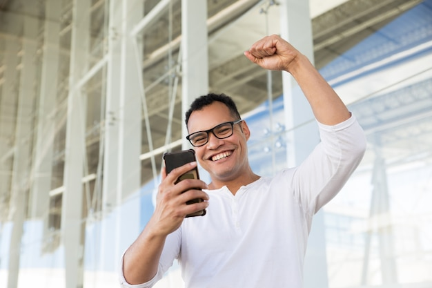 Dolny widok uśmiechnięty młody człowiek wykończeniowa rozmowa telefonicza, exulting Darmowe Zdjęcia