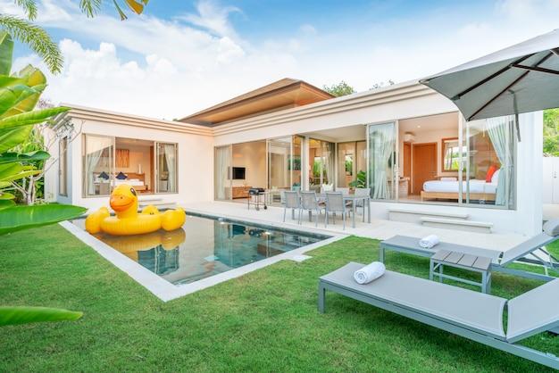 Dom lub dom projekt zewnętrzny przedstawiający tropikalną willę przy basenie z ogrodem zieleni, solarium, parasolem, ręcznikami basenowymi i kaczką Premium Zdjęcia