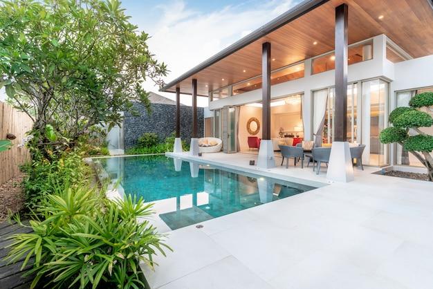 Dom lub dom projekt zewnętrzny przedstawiający tropikalną willę przy basenie z ogrodem zieleni, Premium Zdjęcia