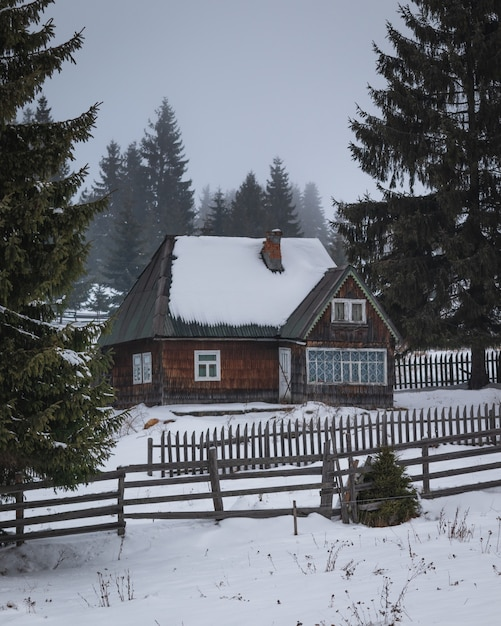 Dom Z Drewnianym Płotem Pośrodku śniegu I Sosen Darmowe Zdjęcia