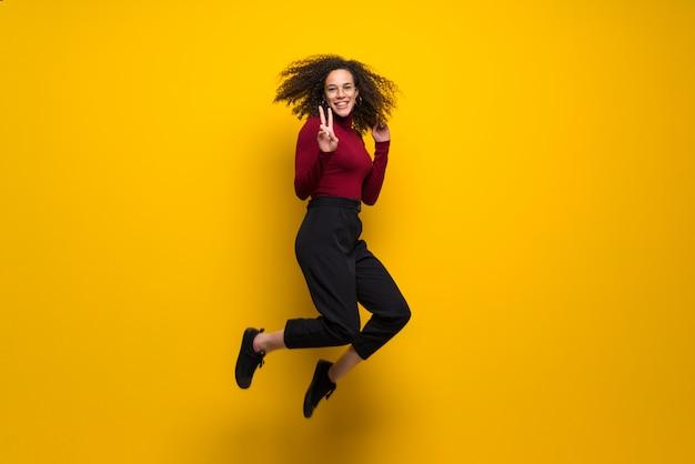 Dominikańska Kobieta Skacze Nad Odosobnioną Kolor żółty ścianą Z Kędzierzawym Włosy Premium Zdjęcia
