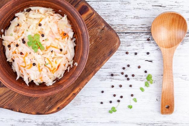 Domowa marynowana kapusta, kiszona kapusta w drewnianym stole kuchennym miski Premium Zdjęcia