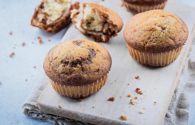 Domowe babeczki ze słodkiej czekolady waniliowej z dwóch rodzajów ciasta ze słoikiem z kamienia na drewnianym stole na niebieskim kamiennym stole Premium Zdjęcia