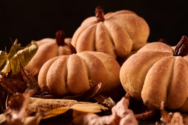 Domowe ciasteczka w kształcie dyni w jesienne liście. halloweenowi handmade ciastka na stole, zamykają up Premium Zdjęcia