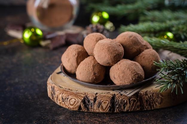 Domowe czekoladowe trufle na papierze na kamiennym betonowym stole z świąteczną dekoracją świąteczną. świąteczny deser Premium Zdjęcia