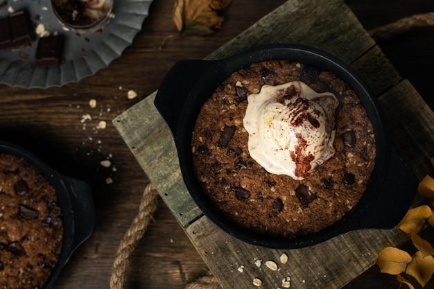 Domowe Jedzenie Komfortowe, Gigantyczne Ciastko Na Patelni Z Kawałkami Czekolady I Lodami, Widok Z Góry Premium Zdjęcia