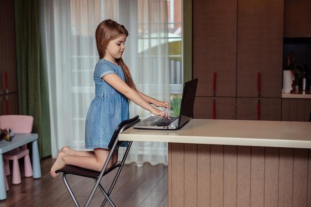 Domowe Nauczanie Na Odległość Dzieci Podczas Kwarantanny. Szczęśliwa Dziecko Dziewczyna Z Długimi Włosami W Dżinsach Sukienka Odrabiania Lekcji Za Pomocą Laptopa Siedząc W Domu W Kuchni Premium Zdjęcia